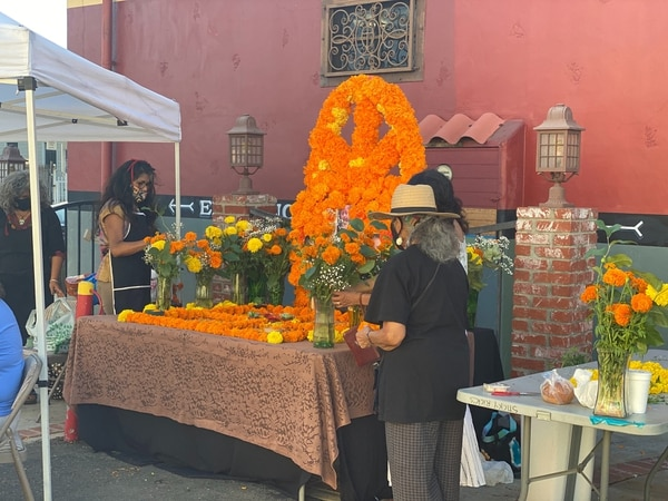 The woman in the hat is Ofelia who is adorning the altar with Cempasúchitl flowers in the parking lot of El Gallo Grill in East Los Angeles. (Photo by Frank Rojas)