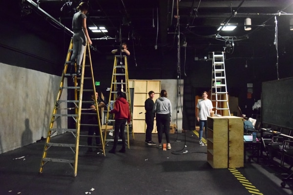 Brand New Theatre executive board members taking down lighting instruments. (Photo by Steven Vargas)