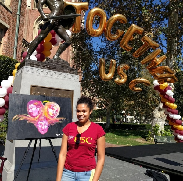 USC Junior Public Relations Major Sarah Reyes Stands with her painting representing diversity and inclusion. (Billy Rehbock/USC Annenberg Media)