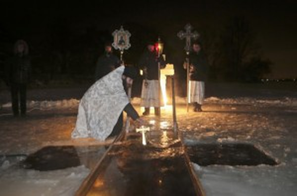 A Russian Orthodox priest blessing water in a river on Russian Orthodox Epiphany in the village (Anorak)