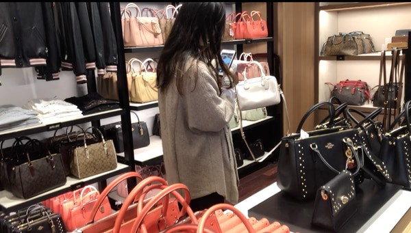 A purchasing agentphotographs a luxury handbag at a store in Southern California to post online and gauge demand among potential customers in China. (Photo by Xinyan Zhang)