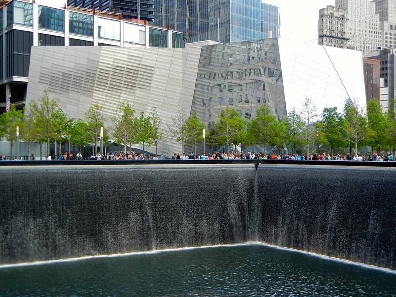A water flows into a pool with buildings and a crowd of people behind it in New York City.