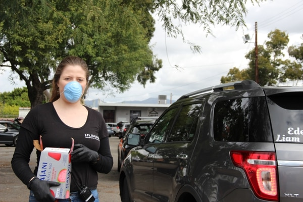 NVCS worker Catalina Roldan wearing a protective mask while distributing food during the drive-thru food bank. (Photo courtesy of Silvia Robles and Catalina Roldan.)