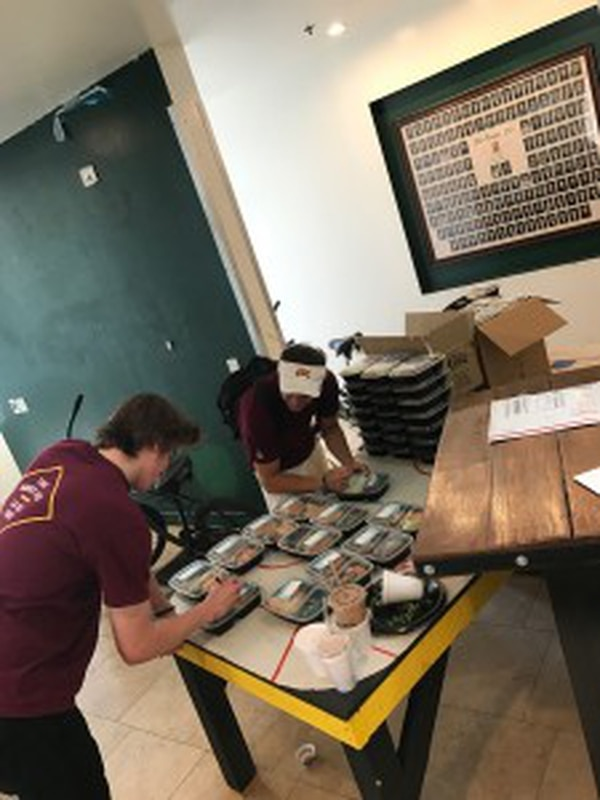 John Depriest and Nick Omsberg getting ready to head out of Phi Psi with packaged meals. (Photo courtesy: Stephen Ruff)