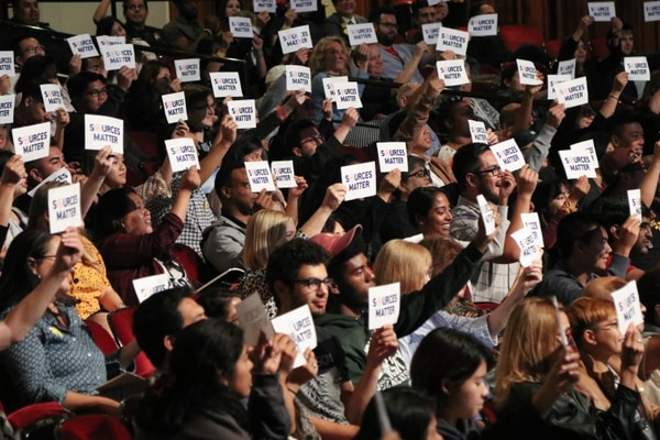 """The crowd at the event holds up cards reading one of the messages of the night, """"Sources Matter""""."""