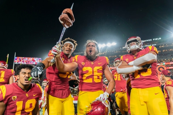 Sophomore inside linebacker Kana'i Mauga shows off two deflated footballs on the Trojan sword. (Photo by Ling Luo)
