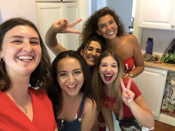 Pooja Goel, pictured with a Tommy Trojan face sticker and holding up a 'fight on' hand sign, poses with other USC students, including her best friend, Kirsten Briggs, pictured in the front with a silver necklace.