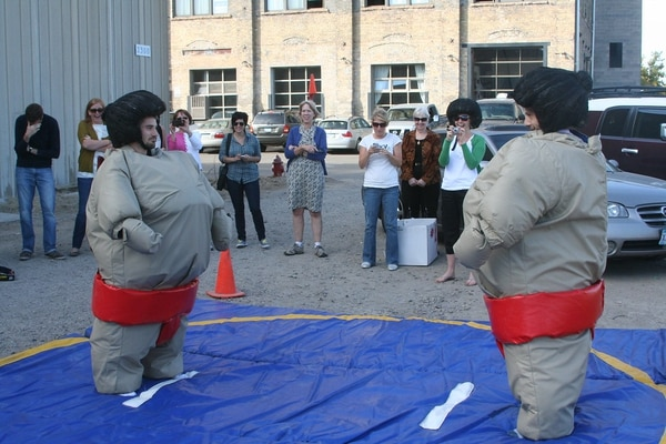 Office workers dressed in inflatable sumo costumes in a parking lot. (