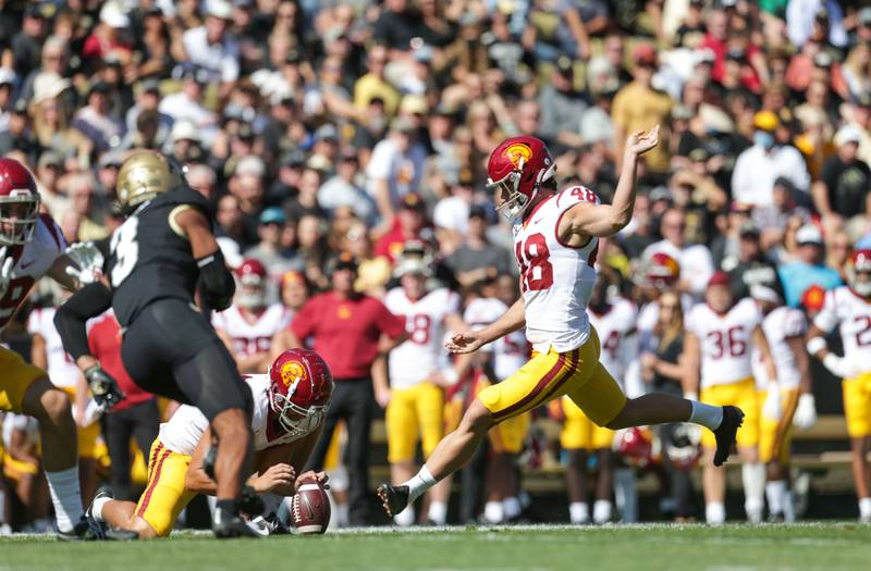 A photo of USC sophomore Parker Lewis attempting a kick in a white jersey, cardinal helmet and gold pants.