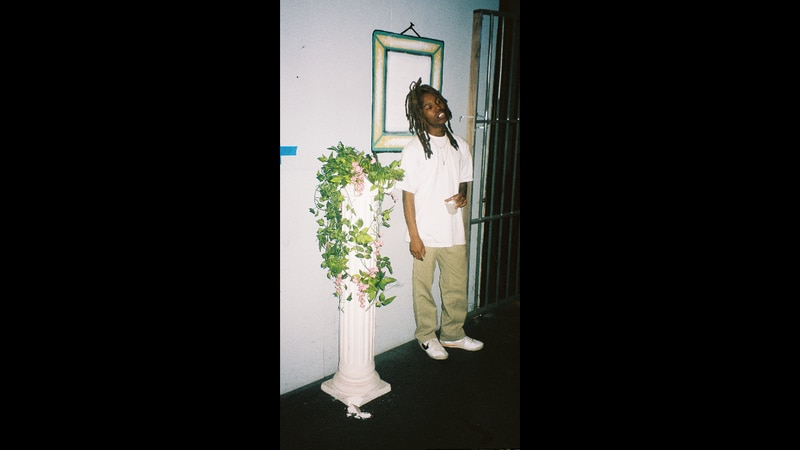Photo of the rapper Mavi next to a potted plant.