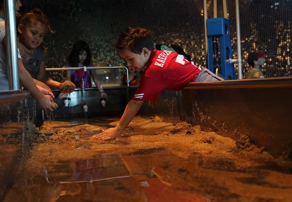 Three children experiment with water and sand at the California Science Center's River Zone exhibit. | Ciara Lunger