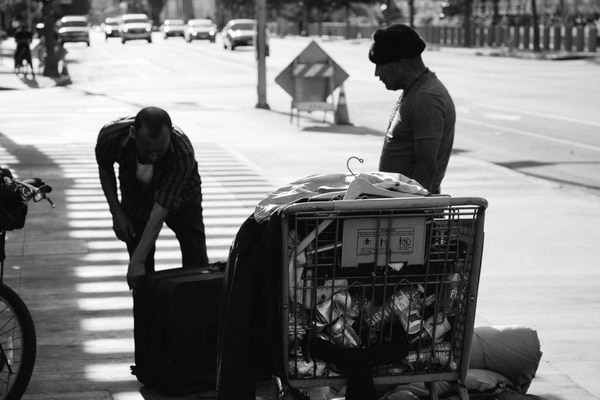 A homeless individual helps another with a move to new location