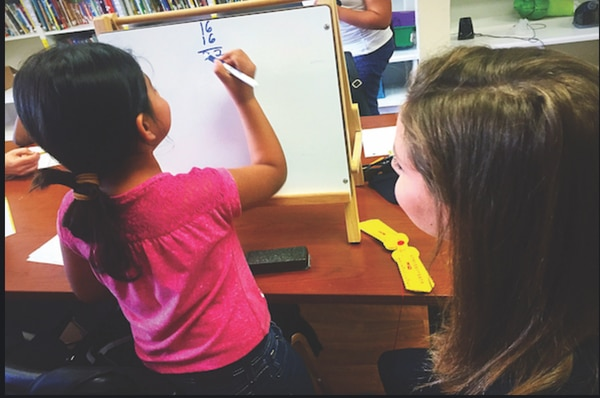 A child practices math on a whiteboard at School on Wheels. (Image courtesy of School on Wheels)