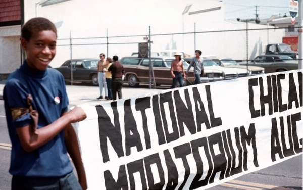 "An unknown teenaged kid holds a sign reading ""National Chicano Moratorium Aug 29"". (Photo by George Rodriguez)"