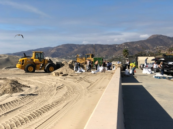Malibu residents and LA County workers shovel sand into bags for others to use to protect their homes from tonight's rainfall which will potentially create floods. (Annenberg Media/ Jesús Alvarado)