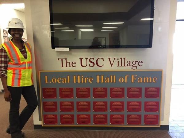 "Theodora Oyie stands next to a ""Local Hire Hall of Fame"" installation honoring contractors who exceeded local hiring goals outlined in the USC Village development agreement. Photo contributed by: Theodora Oyie"