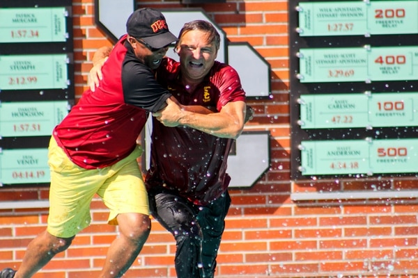 Vavic celebrates by pulling USC Athletic Director Lynn Swann into the pool. (Jodee Storm Sullivan/Annenberg Media)